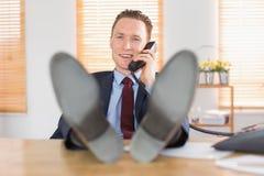 Χαλαρωμένος επιχειρηματίας που κάνει ένα τηλεφώνημα Στοκ Φωτογραφία