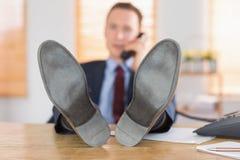 Χαλαρωμένος επιχειρηματίας που κάνει ένα τηλεφώνημα Στοκ εικόνες με δικαίωμα ελεύθερης χρήσης