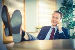 Χαλαρωμένος επιχειρηματίας που κάνει ένα τηλεφώνημα Στοκ Εικόνες
