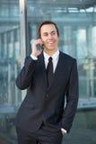 Χαλαρωμένος επιχειρηματίας που χαμογελά και που μιλά στο κινητό τηλέφωνο Στοκ φωτογραφία με δικαίωμα ελεύθερης χρήσης