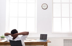 Χαλαρωμένος μαύρος επιχειρηματίας με το lap-top στο σύγχρονο άσπρο γραφείο Στοκ Εικόνες