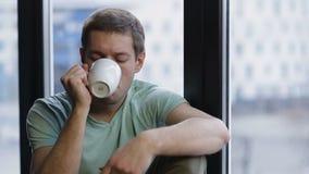 Χαλαρωμένος νέος καφές κατανάλωσης hipster κοντά στο παράθυρο φιλμ μικρού μήκους