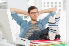 Χαλαρωμένος περιστασιακός νεαρός άνδρας με τα πόδια στο γραφείο Στοκ Φωτογραφίες