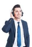 Χαλαρωμένος χαμογελώντας επιχειρηματίας ή τραπεζίτης που απολαμβάνει τη μουσική στο headphon Στοκ εικόνα με δικαίωμα ελεύθερης χρήσης