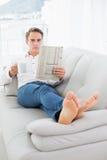 Χαλαρωμένο άτομο με το φλυτζάνι καφέ διαβάζοντας την εφημερίδα στον καναπέ Στοκ Φωτογραφίες