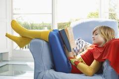 Χαλαρωμένο αγόρι στην ανάγνωση κοστουμιών υπερανθρώπων Στοκ φωτογραφία με δικαίωμα ελεύθερης χρήσης