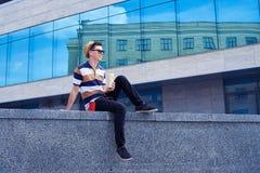 Χαλαρωμένο αρσενικό που τρώει τα τρόφιμα οδών και που πίνει τον καφέ μέσα κεντρικός Στοκ Εικόνες