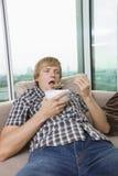 Χαλαρωμένο μέσος-ενήλικο άτομο με το κύπελλο των δημητριακών στο καθιστικό στο σπίτι στοκ φωτογραφίες με δικαίωμα ελεύθερης χρήσης