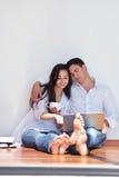 Χαλαρωμένο νέο ζεύγος που εργάζεται στο φορητό προσωπικό υπολογιστή στο σπίτι στοκ εικόνες