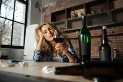 Χαλαρωμένο ξανθό θηλυκό γυαλί εκμετάλλευσης με το κρασί στοκ εικόνες