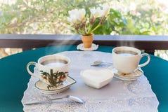 Χαλαρώνοντας χρόνος και ευτυχία με δύο φλυτζάνια του μαύρου καφέ με τη ζάχαρη Στοκ Φωτογραφία