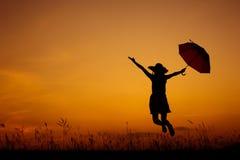 Χαλαρώστε τη σκιαγραφία άλματος και ηλιοβασιλέματος γυναικών ομπρελών Στοκ Εικόνες