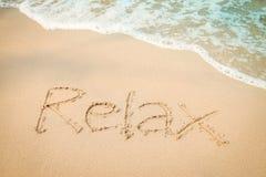Χαλαρώστε το χέρι μηνυμάτων γράφοντας στην παραλία άμμου στοκ φωτογραφίες