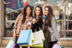 Χαλασμένες γυναίκες που χρησιμοποιούν τις πιστωτικές κάρτες τους σε μια λεωφόρο Στοκ εικόνες με δικαίωμα ελεύθερης χρήσης