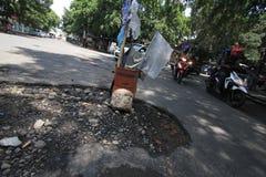 Χαλασμένοι δρόμοι που διακινδυνεύουν τους χρήστες του οδικού δικτύου στοκ φωτογραφία