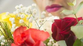 Χείλια γυναίκας με τα λουλούδια στο μέτωπο στοκ φωτογραφίες