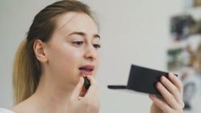 Χείλια Makeup ομορφιάς Γυναίκα που εφαρμόζει το κόκκινο κραγιόν στο πλήρες χείλι απόθεμα βίντεο