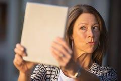 Χείλια Puckering γυναικών στην ταμπλέτα Στοκ εικόνες με δικαίωμα ελεύθερης χρήσης