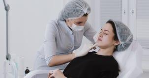 Χειλική αύξηση Το cosmetologist γιατρών κάνει τη διαδικασία χειλικής αύξησης μιας όμορφης γυναίκας σε ένα σαλόνι ομορφιάς απόθεμα βίντεο