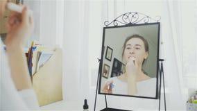 Χειλική προσοχή Γυναίκα που εφαρμόζει την κινηματογράφηση σε πρώτο πλάνο χειλικού βάλσαμου προστασίας φιλμ μικρού μήκους