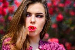 Χειλικό βάλσαμο Κορίτσι με το λουλούδι στο στόμα Κόκκινο κραγιόν Φυσική έννοια καλλυντικών Φροντίδα δέρματος Makeup r Αρκετά στοκ φωτογραφία