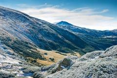 Χειμερινά βουνά και ηλιόλουστη πράσινη κοιλάδα Στοκ Φωτογραφία