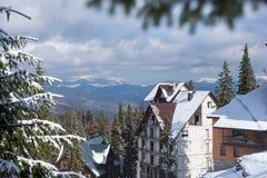 Χειμερινά βουνά κοντά στα εξοχικά σπίτια μεταξύ χιονισμένα fir-trees, φ Στοκ φωτογραφίες με δικαίωμα ελεύθερης χρήσης