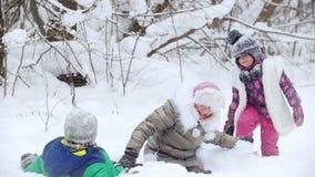 Χειμερινά δασικά εύθυμα χαμογελώντας παιδιά στα φωτεινά ενδύματα που παίζουν με το χιόνι Κτύποι μικροί κοριτσιών πέρα από τον αδε απόθεμα βίντεο