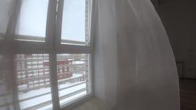 Χειμερινή άποψη παραθύρων με τα άσπρους έπιπλα, τους τοίχους, το λαμπτήρα και τους τυφλούς, που κυματίζουν στον αέρα φιλμ μικρού μήκους