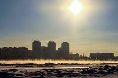 Χειμερινή εικονική παράσταση πόλης στο ηλιοβασίλεμα, σπίτια στο υπόβαθρο ενός φωτοστεφάνου - ένα ενδιαφέρον φυσικό φαινόμενο Η έν ελεύθερη απεικόνιση δικαιώματος