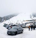 Χειμερινή ημέρα την κλίση χιονιού και σκι που βλέπει με από την περιοχή χώρων στάθμευσης με το Κ Στοκ Φωτογραφία