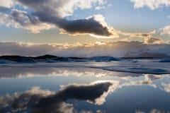 Χειμερινή λιμνοθάλασσα αντανάκλασης με τον ήλιο πίσω από τα άσπρα σύννεφα Στοκ εικόνα με δικαίωμα ελεύθερης χρήσης