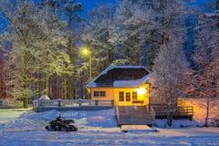 Χειμερινή ιστορία - όχημα για το χιόνι κοντά στο άνετο ξύλινο σπίτι και την παγωμένη λίμνη Χιονώδες παγωμένο χειμερινό βράδυ Στοκ εικόνα με δικαίωμα ελεύθερης χρήσης