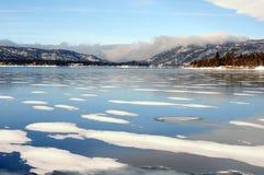 Χειμερινή λίμνη ενάντια στα νεφελώδη βουνά στοκ εικόνα