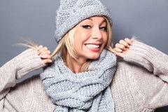 Χειμερινή νέα ξανθή γυναίκα Girly που χαμογελά και που παίζει με την τρίχα στοκ εικόνες