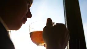 Χειμερινή παγωμένη ημέρα Ο τύπος νωρίς το πρωί που στέκεται στο παράθυρο και το καυτό τσάι κατανάλωσης φιλμ μικρού μήκους