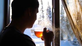 Χειμερινή παγωμένη ημέρα Ο τύπος νωρίς το πρωί που στέκεται στο παράθυρο και το καυτό τσάι κατανάλωσης στοκ εικόνες με δικαίωμα ελεύθερης χρήσης