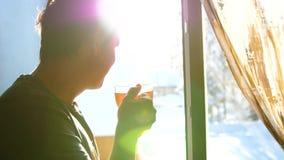 Χειμερινή παγωμένη ημέρα Ο τύπος νωρίς το πρωί που στέκεται στο παράθυρο και το καυτό τσάι κατανάλωσης απόθεμα βίντεο