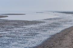 Χειμερινή παραλία με τις απόμακρες σκιαγραφίες ανθρώπων Στοκ Φωτογραφία