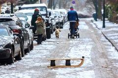 Χειμερινή σκηνή οδών πόλεων με το έλκηθρο και την οικογένεια Στοκ Εικόνες