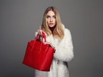 Χειμερινή όμορφη γυναίκα στο παλτό γουνών Πρότυπο κορίτσι μόδας ομορφιάς μοντέρνο ξανθό κορίτσι πολυτέλειας με την κόκκινη τσάντα Στοκ Φωτογραφία