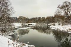 Χειμερινός δασικός ποταμός με τις χιονισμένες τράπεζες Στοκ Φωτογραφία