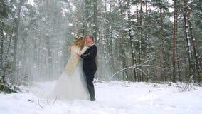 Χειμερινός δασικός πυροβολισμός του νέου ζεύγους που έχει τη διασκέδαση κάτω από τις χιονοπτώσεις κίνηση αργή