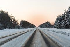 Χειμερινός δρόμος με τον πάγο στην άσφαλτο, δέντρα κάτω από το χιόνι κατά τη διάρκεια του χειμερινού παγετού Στοκ Εικόνες