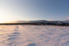 Χειμερινός δρόμος στο δασικό τοπίο ηλιοβασιλέματος Χιονισμένο πεδίο Στοκ Φωτογραφίες