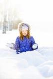 Χειμερινό πορτρέτο ενός χαμογελώντας κοριτσιού, που κάθεται στο χιόνι PA Στοκ Φωτογραφία