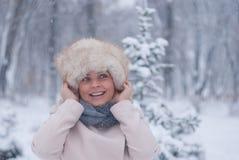 Χειμερινό πορτρέτο μιας γυναίκας στο άσπρο παλτό κατά τη διάρκεια των χιονοπτώσεων σε ένα πάρκο Στοκ Φωτογραφία