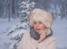 Χειμερινό πορτρέτο μιας γυναίκας στο άσπρο παλτό κατά τη διάρκεια των χιονοπτώσεων σε ένα πάρκο Στοκ Φωτογραφίες