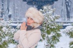 Χειμερινό πορτρέτο μιας γυναίκας στο άσπρο παλτό κατά τη διάρκεια των χιονοπτώσεων σε ένα πάρκο Στοκ φωτογραφία με δικαίωμα ελεύθερης χρήσης