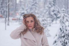 Χειμερινό πορτρέτο μιας γυναίκας στο άσπρο παλτό κατά τη διάρκεια των χιονοπτώσεων σε ένα πάρκο Στοκ Εικόνες